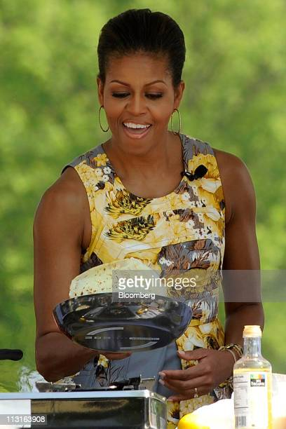 First Lady Michelle Obama flips a crepe at a cooking station during the White House Easter Egg Roll on the South Lawn of the White House in...