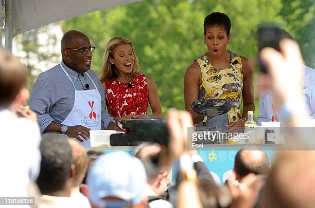 First lady Michelle Obama flips a crepe during a cooking demonstration as Al Roker and Kelly Ripa watch at the White House Easter Egg Roll on the...