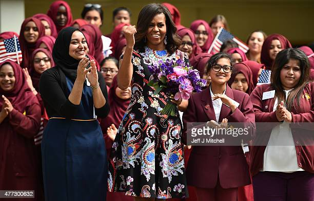 First Lady Michelle Obama gestures and holds flowers as she is received by young students holding the American flag in the courtyard before an event...