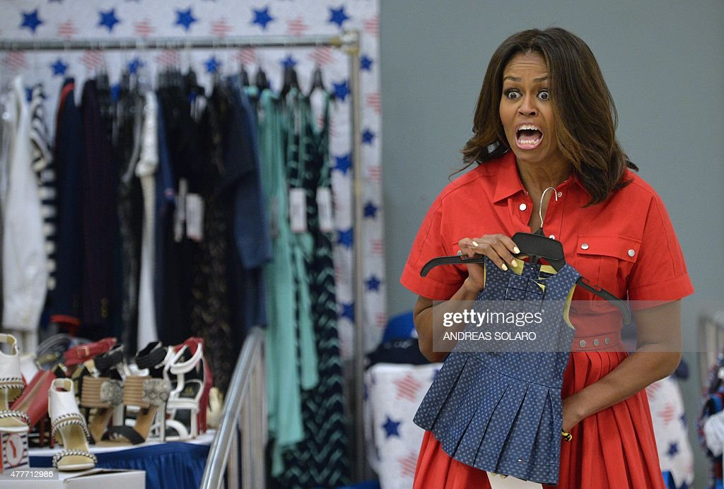 US First Lady Michelle Obama gestures as she holds children's clothing as she meets with women expecting babies at the United States and Nato military base in Vicenza on June 19, 2015 .