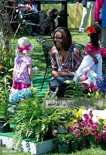 US First Lady Michelle Obama greets a little girl after reading 'My Garden' by Kevin Henkes during the annual Easter Egg Roll at the White House in...