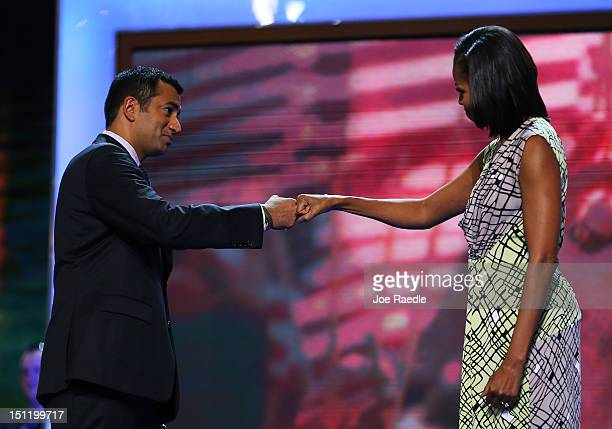 First lady Michelle Obama greets actor Kal Penn on stage during preparations for the Democratic National Convention at Time Warner Cable Arena on...