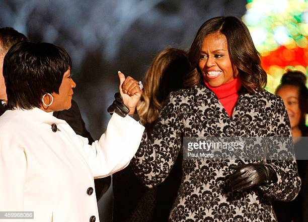 First Lady Michelle Obama greets Patti LaBelle while on stage during the 2014 National Christmas Tree Lighting Ceremony finale at President's Park on...