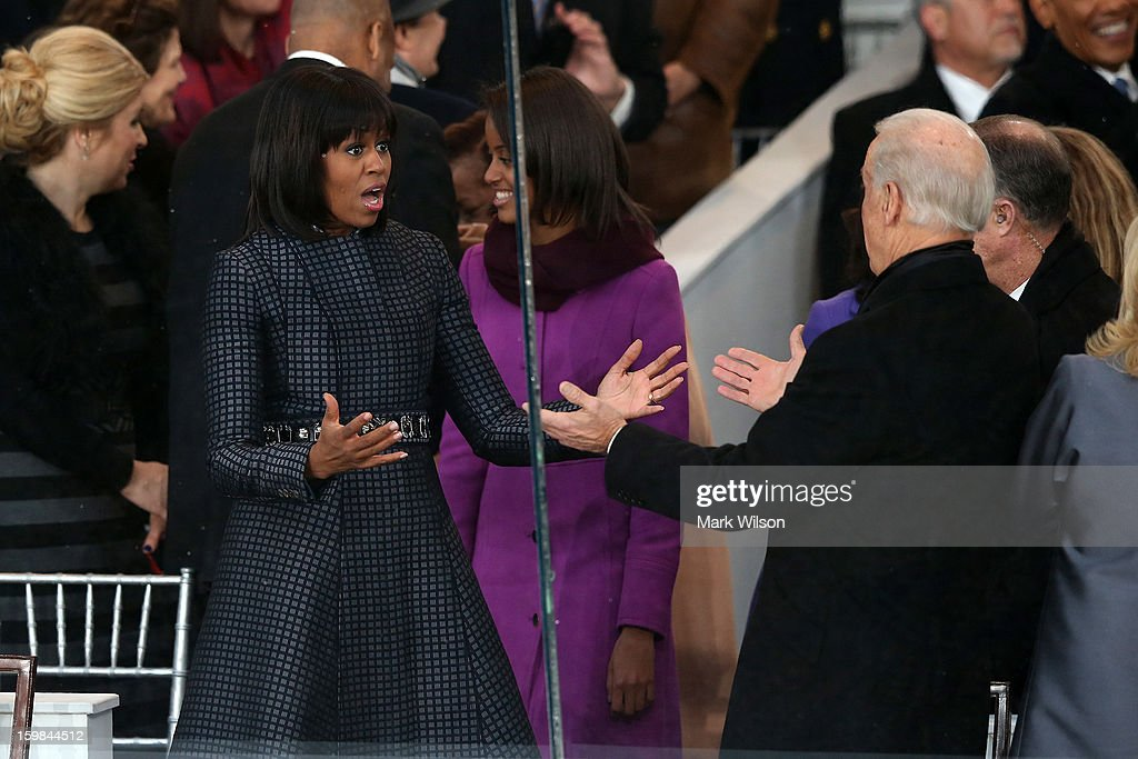 First lady Michelle Obama (L) greets U.S. Vice President Joe Biden on the reviewing stand as the presidential inaugural parade winds through the nation's capital January 21, 2013 in Washington, DC. Barack Obama was ceremonially sworn in for a second term as President of the United States.
