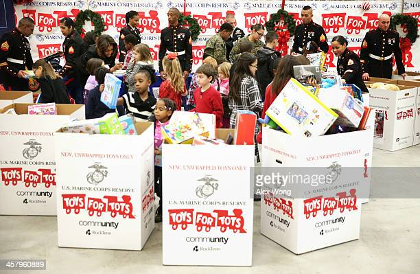 S first lady Michelle Obama helps children to sort gifts for the Marine Corps' Toys for Tots Campaign December 19 2013 at Joint Base AnacostiaBolling...