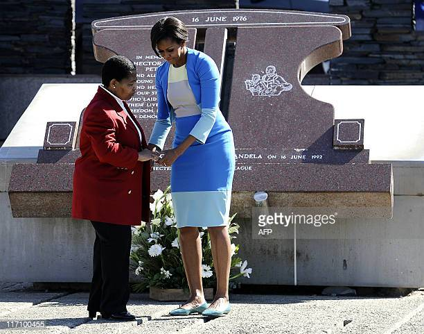 US First Lady Michelle Obama holds hands with Antoinette Sithole sister of Hector Pieterson a 12yearold boy killed during the student uprising in...