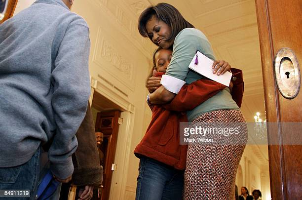First Lady Michelle Obama hugs a student after attending an event in the East Room of the White House on February 18 2009 in Washington DC Mrs Obama...