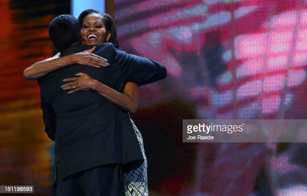 First lady Michelle Obama hugs actor Kal Penn on stage during preparations for the Democratic National Convention at Time Warner Cable Arena on...