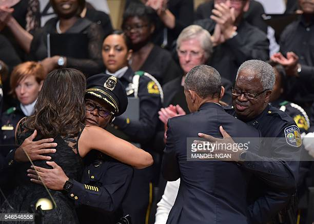 TOPSHOT First Lady Michelle Obama hugs Dallas Police Chief David Brown as US President Barack Obama hugs Dallas Area Rapid Transit Police Chief James...