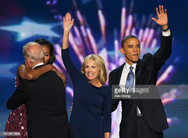 First lady Michelle Obama hugs Democratic vice presidential candidate US Vice President Joe Biden as Second lady Dr Jill Biden waves with Democratic...