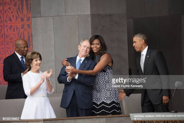 First Lady Michelle Obama hugs former President George W Bush at the opening of the National Museum of African American History and Culture...