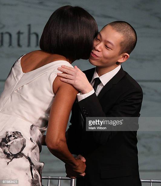 First lady Michelle Obama hugs inaugural dress designer Jason Wu during an event where she donated her inaugural gown to the Smithsonian Museum of...