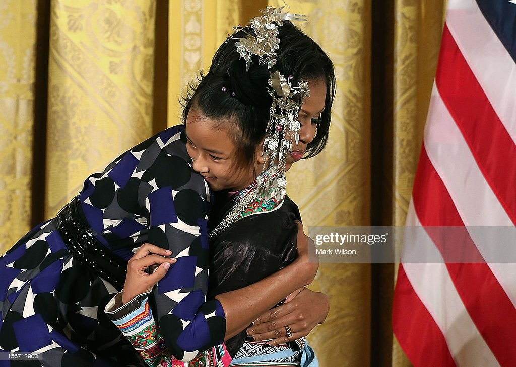 First lady Michelle Obama hugs Lianyun Wu during an awards ceremony for the President's Committee on the Arts and the Humanities in the East Room at the White House on November 19, 2012 in Washington, DC. The first lady talked about the importance of afterschool and out of school arts and humanities education and presented awards recognizing programs across the country that benefit underserved youth.