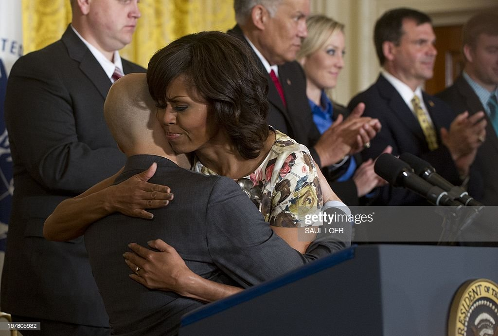 US First Lady Michelle Obama hugs military veteran David Padilla during an event highlighting Joining Forces hiring initiative for military veterans and spouses in civilian jobs in the East Room of the White House in Washington on April 30, 2013. Since President Obama challenged American businesses to hire US military veterans and spouses in August 2011, they have hired or trained 290,000 military veterans and spouses and now pledge to hire or train an additional 435,000 veterans and military spouses by 2018. AFP PHOTO / Saul LOEB