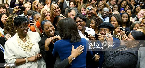 US First Lady Michelle Obama is hugged as she shakes hands with members of the US Secret Service after touring the headquarters in Washington DC...