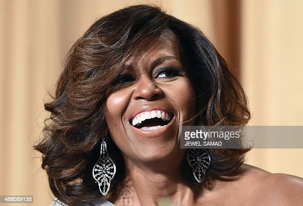 US First Lady Michelle Obama laughs as President Barack Obama tells jokes during the White House Correspondents Association Dinner on May 3 2014 in...