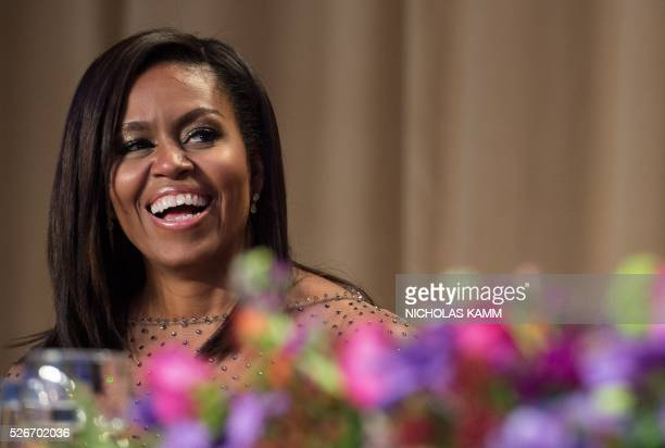US First Lady Michelle Obama laughs at a joke by her husband President Barack Obama during the 102nd White House Correspondents' Association Dinner...