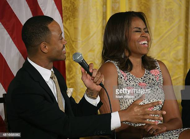 First lady Michelle Obama laughs while E News co anchor Terrence Jenkins speaks during a discussion on higher education n the East Room of the White...