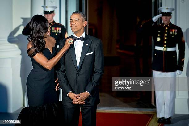 US First Lady Michelle Obama left adjusts US President Barack Obama's bowtie prior to greeting Xi Jinping China's president and Peng Liyuan China's...