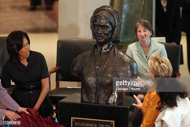 First lady Michelle Obama left and Secretary of State Hillary Clinton right unveil a bust of Sojourner Truth during a ceremony in the new visitor...