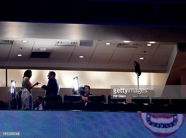 First lady Michelle Obama left does a television interview in the upper decks of the Time Warner Cable Arena before her podium check at the...