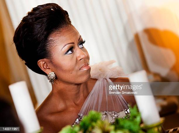 First lady Michelle Obama listens to President Barack Obama speak in the State Dining Room of the White House February 26 2012 in Washington DC...