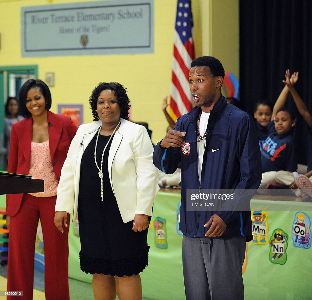 US First Lady Michelle Obama (L) listens to remarks by 2010 Olympian Shani Davis (R) during an event highlighting physical activity as a critical element of the 'Let's Move' initiative on April 21, 2010 in the North East section of Washington, DC. AFP PHOTO / Tim Sloan