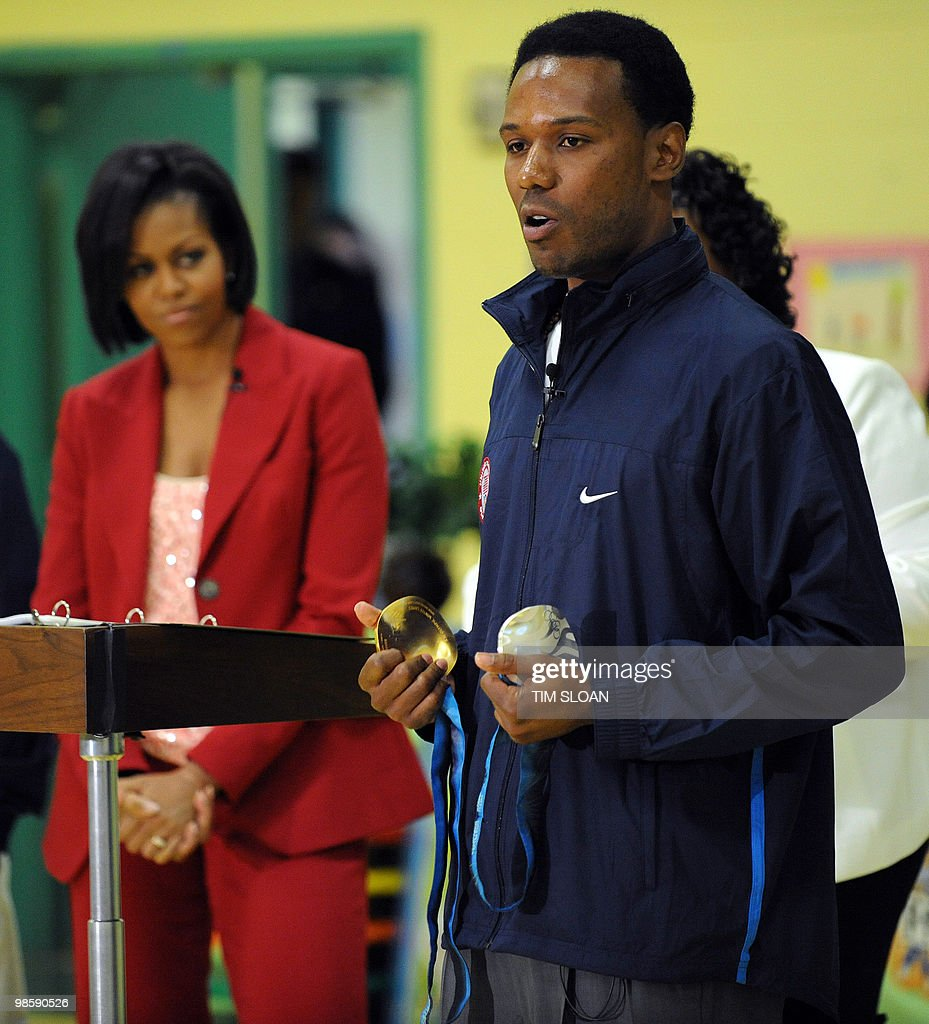 US First Lady Michelle Obama (L) listens to remarks by 2010 Olympian speedskater Shani Davis (R) holding his gold and silver medals during an event highlighting physical activity as a critical element of the 'Let's Move' initiative on April 21, 2010 in the North East section of Washington, DC. AFP PHOTO / Tim Sloan