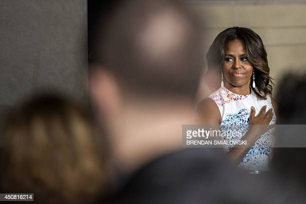 US First Lady Michelle Obama listens to the National Anthem during a naturalization ceremony at the National Archives June 18 2014 in Washington DC...