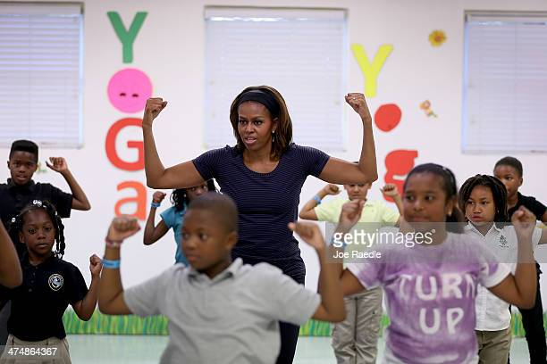 First Lady Michelle Obama participates in a yoga class during a visit to the Gwen Cherry Park NFL/YET Center on February 25 2014 in Miami Florida The...