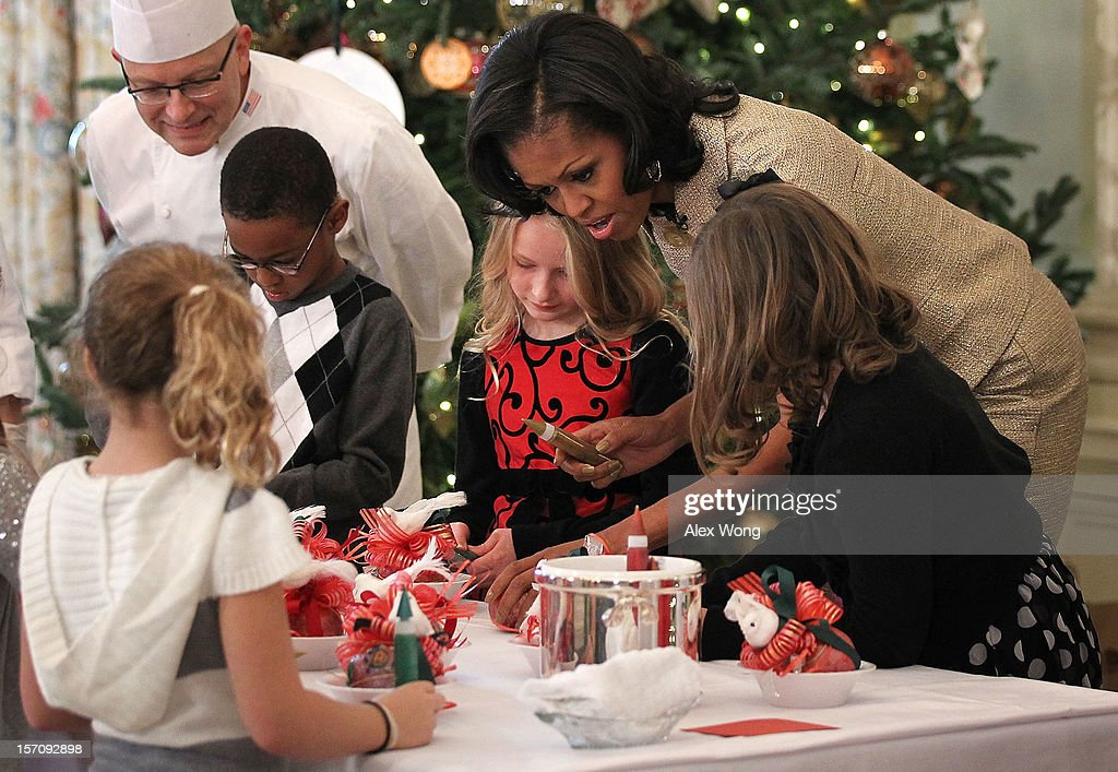 U.S. first lady Michelle Obama participates in craft activities with military children at the State Dining Room after a preview of the 2012 White House holiday decorations November 28, 2012 at the White House in Washington, DC. The first lady welcomed military families, including Gold Star and Blue Star parents, spouses and children, to the White House for the first viewing of the 2012 holiday decorations. The theme for the White House Christmas 2012 is 'Joy to All.'