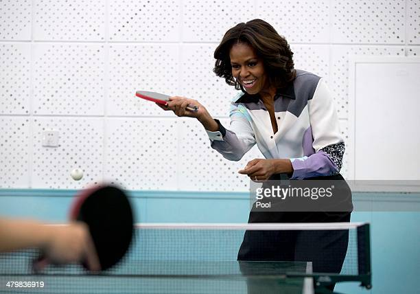 First lady Michelle Obama plays table tennis as she visit to the Beijing Normal School, a school that prepares students to attend university abroad,...
