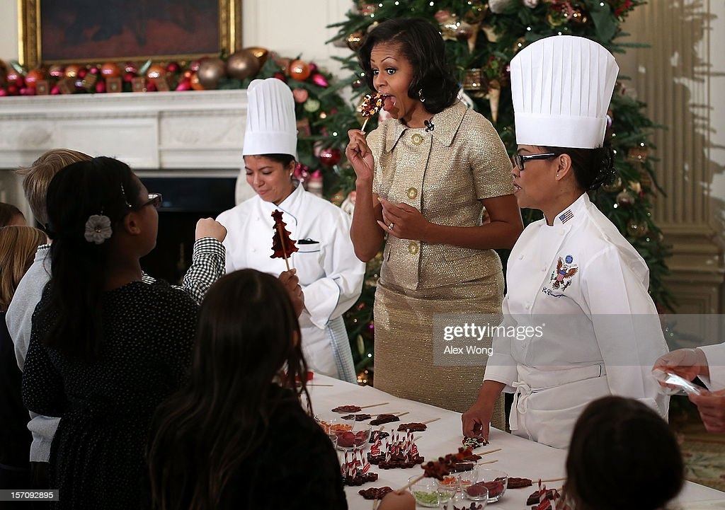 U.S. first lady Michelle Obama pretends to eat a holiday dessert as she participates in craft activities with military children at the State Dining Room after a preview of the 2012 White House holiday decorations November 28, 2012 at the White House in Washington, DC. The first lady welcomed military families, including Gold Star and Blue Star parents, spouses and children, to the White House for the first viewing of the 2012 holiday decorations. The theme for the White House Christmas 2012 is 'Joy to All.'