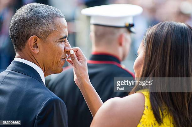 First Lady Michelle Obama primps US President Barack Obama as they wait to welcome Prime Minister Lee Hsien Loong and Mrs Lee Hsien Loong of...