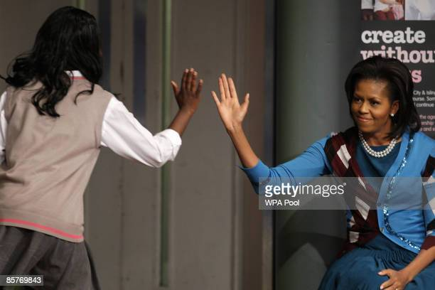 First Lady Michelle Obama raises her arm to touch hands with a student during a visit to the Elizabeth Garrett Anderson Secondary School on April 2,...