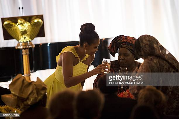US first lady Michelle Obama raises her glass for a toast during a dinner for participants of the US Africa Leaders Summit August 5 2014 in...