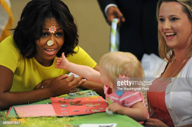 First Lady Michelle Obama reacts to having stickers put on her face by Lilly Oppelt as she is held by her mother Amy Oppelt of South Bend IN as the...