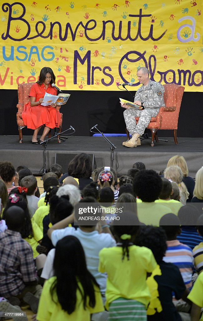 US First Lady Michelle Obama (L) reads a book of fairy tales to children during a visit to the United States and Nato military base in Vicenza on June 19, 2015.