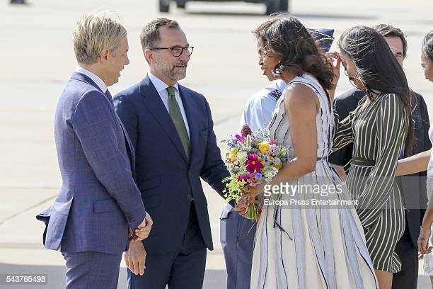 First Lady Michelle Obama receives flowers with her daughter Malia Obama at Torrejon Air Force Base by US ambassador James Costos and Michael Smith...
