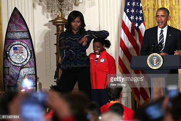 S first lady Michelle Obama rests her elbow on the head of Olympian Simone Biles as President Barack Obama speaks during an East Room event at the...
