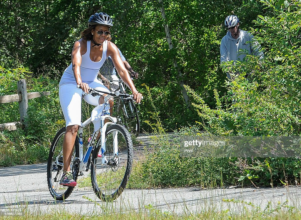 First lady Michelle Obama (L) rides a bike during a vacation on Martha's Vineyard August 16, 2013in West Tisbury, Massachusetts. Obama and his family are on a weeklong vacation.