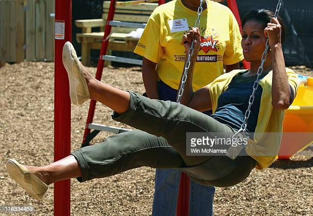 S first lady Michelle Obama rides in a swing while helping to construct a playground at the Imagine Southeast Public Charter Elementary School June...