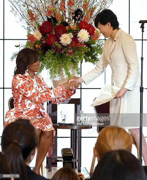 US first lady Michelle Obama shakes hands with Japanese first lady Akie Abe after Abe's speech during the JapanUS joint girls education event at...