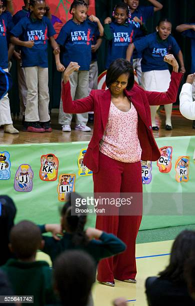First lady Michelle Obama shows off her muscles along with the children at the DC River Terrace School at an event to promote physical fitness and...