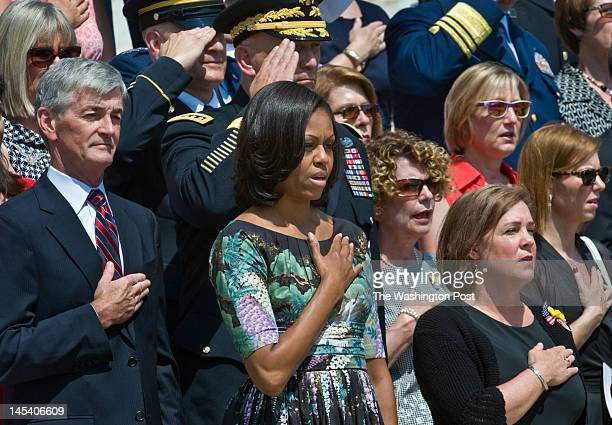 First Lady Michelle Obama sings the National Anthem along with others at a wreath laying ceremony at Arlington National Cemetery Monday May 28 2012...