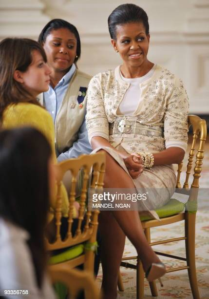 First Lady Michelle Obama sits with a group of young women from the White House leadership and mentoring program during a presentation on the history...
