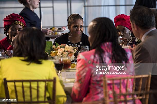 US first lady Michelle Obama sits with Salma Kikwete of Tanzania Gertrude Hendrina Mutharika of Malawi and others talk during lunch at the first lady...
