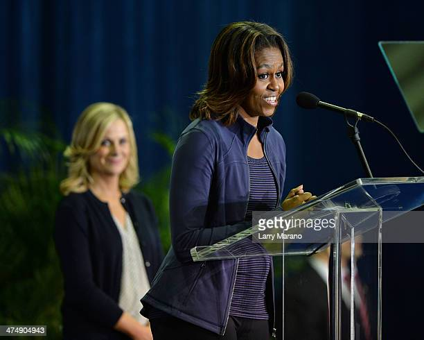 First Lady Michelle Obama speaks as Amy Poehler listens during a visit to the Gwen Cherry Park NFL/YET Center as she celebrates the 4th Anniversary...