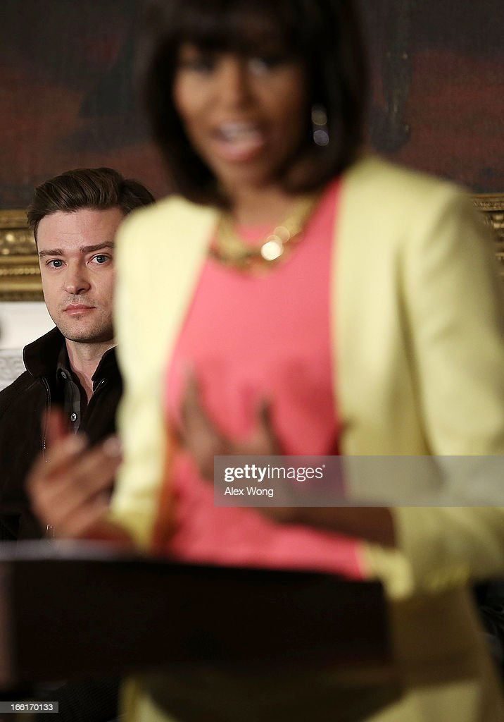 U.S. first lady Michelle Obama (R) speaks as musician Justin Timberlake (L) listen during an interactive student workshop at the State Dining Room of the White House April 9, 2013 in Washington, DC. The first lady hosted middle and high school students from across the country to take part in the workshop on 'Soulsville,