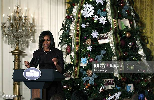 S first lady Michelle Obama speaks during a preview of the 2014 holiday decorations at the East Room of the White House December 3 2014 in Washington...